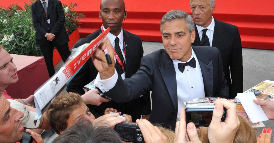 George Clooney d autgrafos a fs ao chegar para a cerimnia de abertura do Festival de Veneza de 2011. Seu filme, 