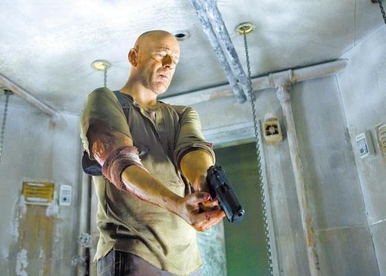 O ator Bruce Willis durante cena do filme Duro de Matar 4.0 (2007), dirigido por Len Wiseman