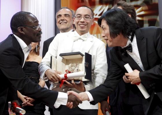 Cineastas se cumprimentam em frente ao vencedor da Palma de Ouro, o tailandês Apichatpong Weerasethakul (23/05/2010)