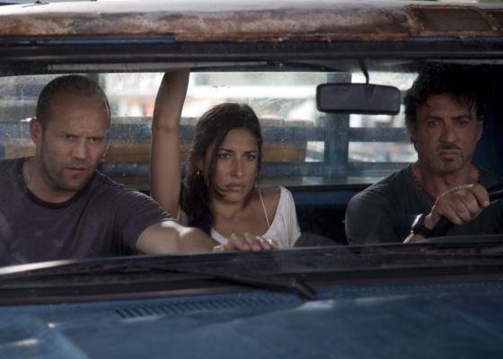 Jason Statham (à esquerda), Gisele Itiè (centro) e Sylvester Stallone (à direita) em cena de ''Os Mercenários''