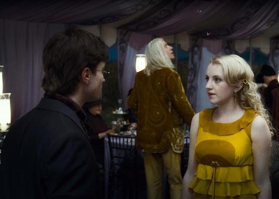Harry Potter (Daniel Radcliffe) conversa com Luna Lovegood (Evanna Lynch) em ''Relíquias da Morte - Parte 1. No fundo, o personagem Xenofílio Lovegood (Rhys Ifans)