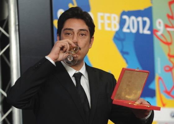 """O diretor português Miguel Gomes festeja o prêmio Alfred Bauer, por """"Tabu"""", com champanhe (18/2/2012)"""