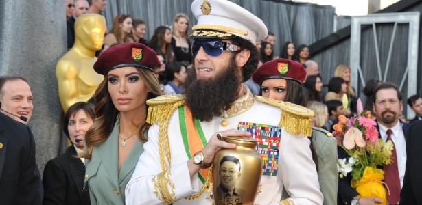 """O comediante Sacha Baron Cohen chega à cerimônia do Oscar 2012 vestido como """"O Ditador"""" e segurando uma urna representando as cinzas do ditador coreano Kim Jong Il; ele jogou as cinzas sobre o apresentador do """"E!"""", Ryan Seacrest (26/2/12)"""
